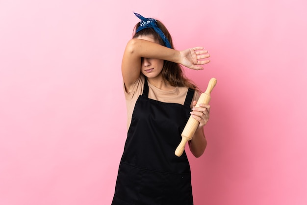 Young woman holding a rolling pin covering eyes by hands