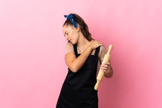 Young woman holding a rolling pin suffering from pain in shoulder for having made an effort