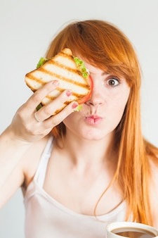 Young woman holding sandwich in front of her eyes