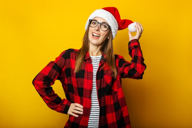 Молодая женщина, держащая шляпу санта-клауса и красную клетчатую рубашку