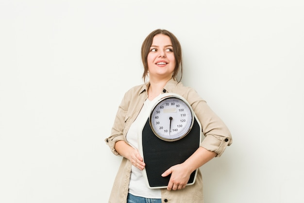 Young woman holding a scale looks aside smiling, cheerful and pleasant.
