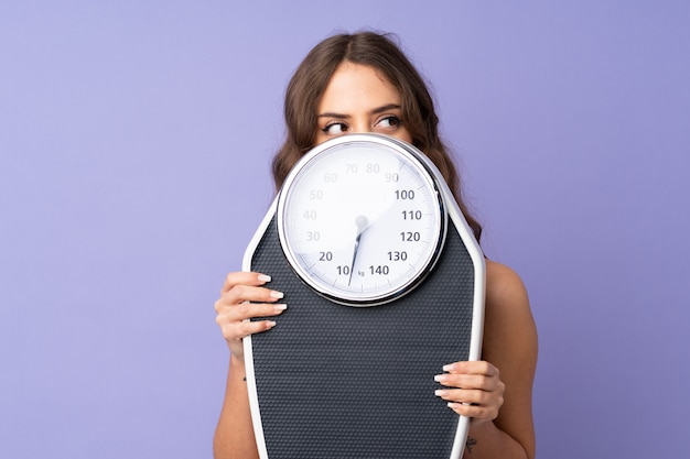 Young woman holding scale