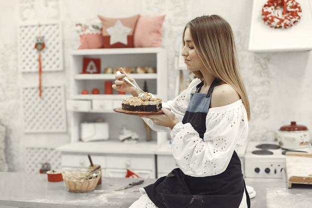 キッチンで自作のケーキを保持している若い女性