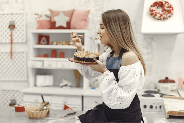 Young woman holding self-made cake in the kitchen