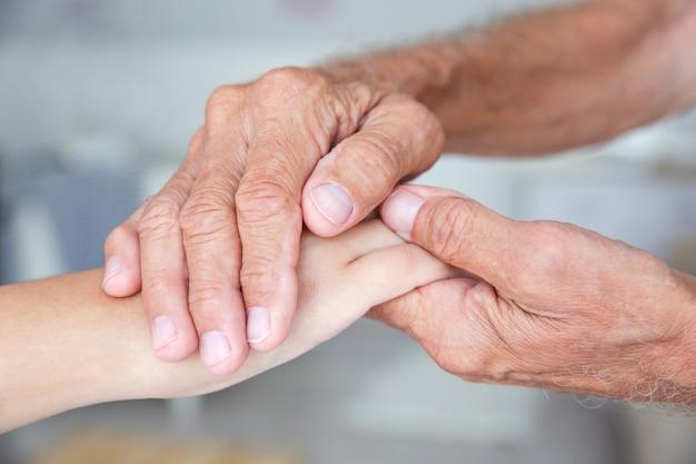 Молодая женщина, держащая руки старшего человека, крупным планом