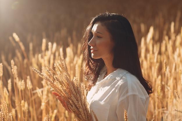 農業分野で小麦の穂の束を保持している若い女性
