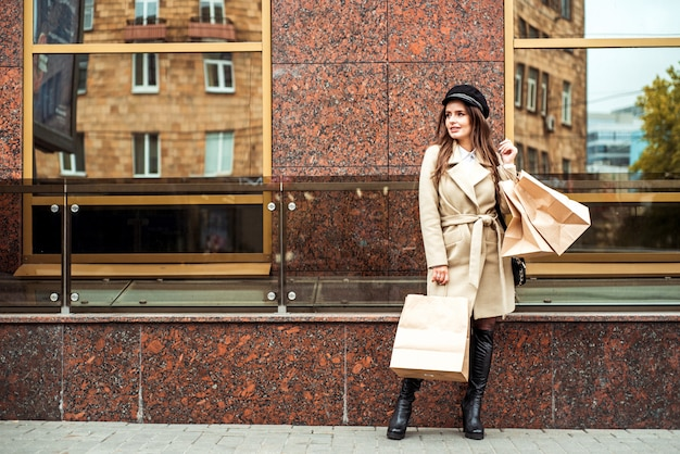 Young woman holding shoopping bags in the city street. smiling lady is running with big bags in metropolis .consumerism, shopping, sales, lifestyle concept
