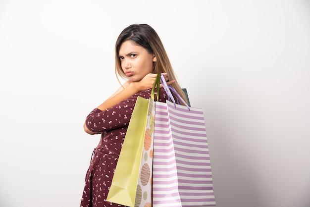 흰 벽에 쇼핑 가방을 들고 젊은 여자.
