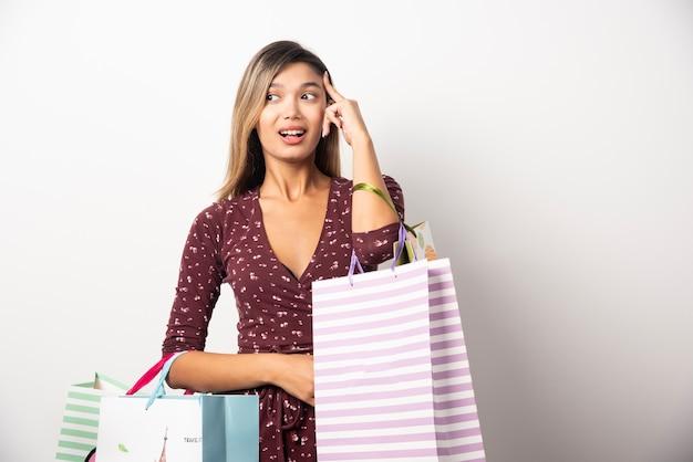 白い壁にショップバッグを保持している若い女性。