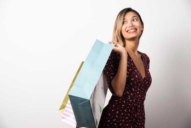 Young woman holding shop bags on white wall.
