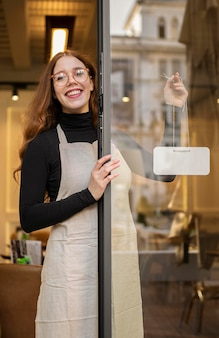 Young woman holding shop sign