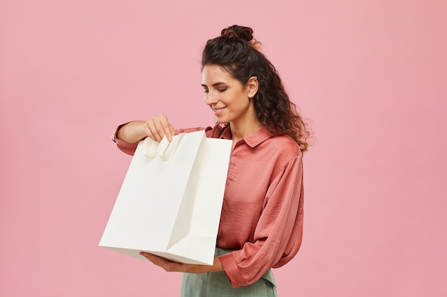 Young woman holding shopping bag in her hands and looking into it isolated on pink background