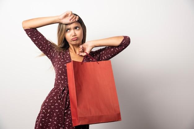 흰 벽에 쇼핑백을 들고 젊은 여자.