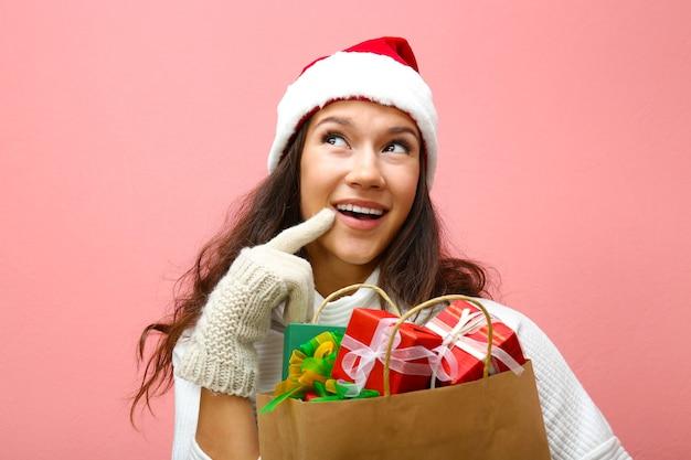 분홍색 배경에 크리스마스 선물이 든 쇼핑백을 들고 있는 젊은 여성