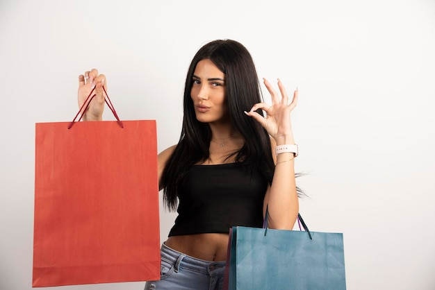 Молодая женщина, держащая хозяйственные сумки и показывающая одобренный знак. фото высокого качества