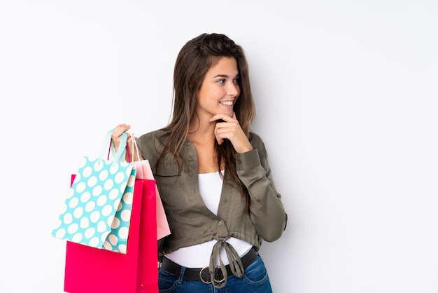 Young woman holding shopping bags over isolated wall