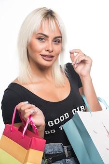 白い背景の上の買い物袋を保持している若い女性。高品質の写真