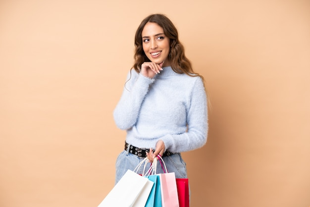 Young woman holding shopping bags and thinking