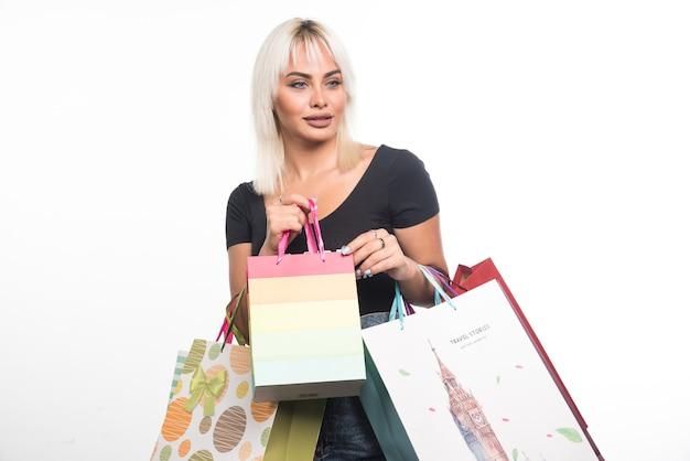 Giovane donna che tiene i sacchetti della spesa sulla parete bianca.