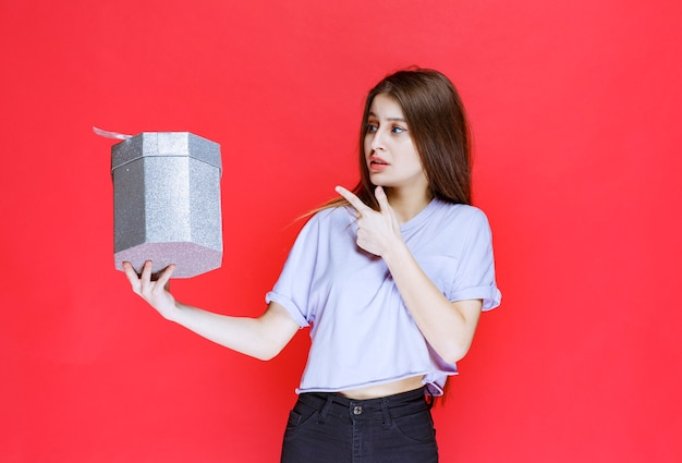 Young woman holding a silver gift box and feeling happy.