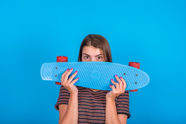 Young woman holding skateboard in front of face on blue background