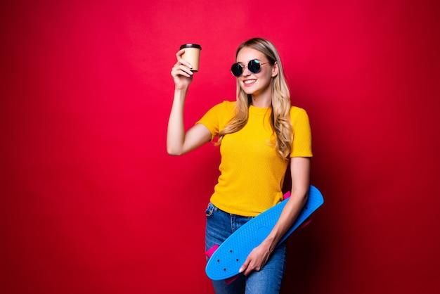Giovane donna che tiene lo skateboard sulla spalla e caffè isolato contro il muro rosso