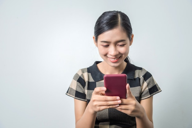 Молодая женщина, держа смартфон и общаться с друзьями, студия выстрел, используя мобильный телефон для проверки новой подачи.