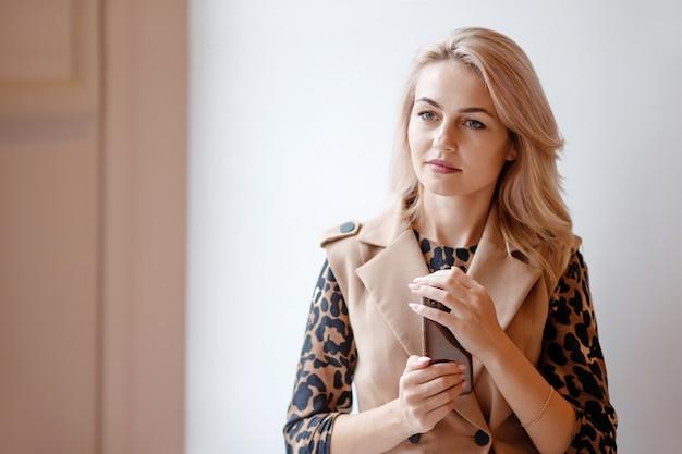 美容室で手でスマートフォンを保持している若い女性。思慮深い表情