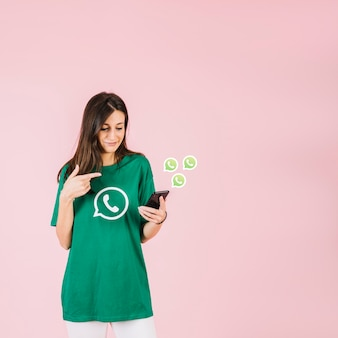 Young woman holding smartphone near whatsapp icon