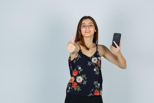 Giovane donna che tiene smartphone, mostra pollice in camicetta, gonna e sembra allegra. vista frontale.