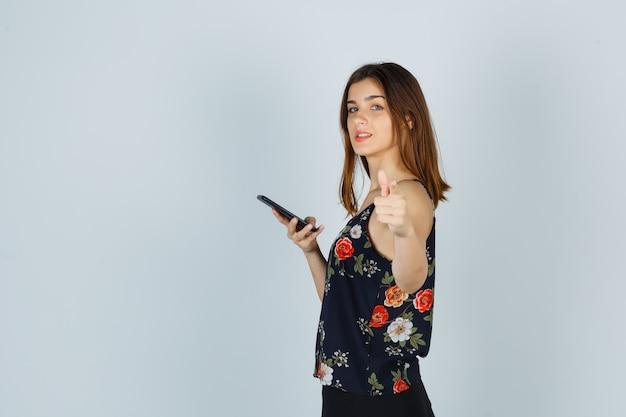 스마트폰을 들고 있는 젊은 여성, 블라우스, 치마를 입고 자신감을 보이고 있습니다.