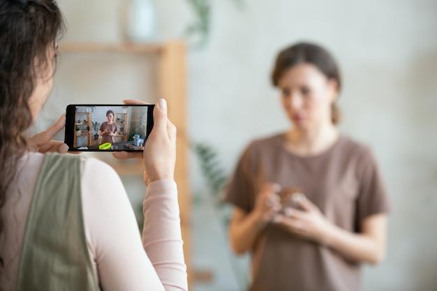 テーブルのそばに立っている間カメラを見ているドライフルーツを含む小さなボウルで女性を撮影しながらスマートフォンを保持している若い女性