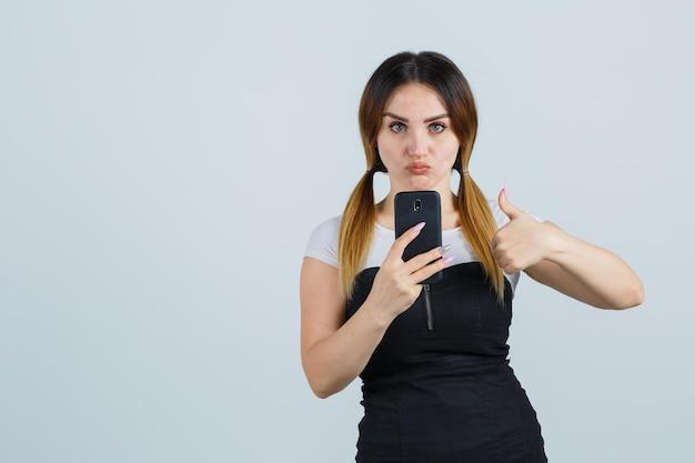 Giovane donna che tiene smartphone mentre mostra i pollici in su