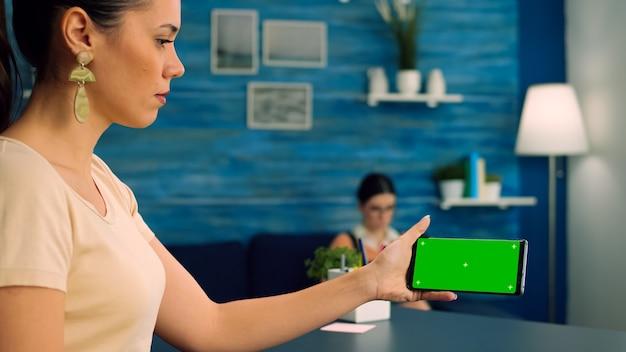 녹색 화면 크로마 키 디스플레이가있는 스마트 폰을 들고 젊은 여자가 책을 읽는 동안 인터넷에서 온라인 정보를 검색합니다.