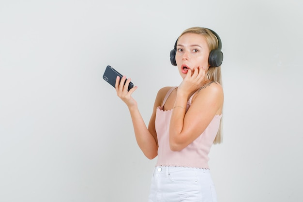 一重項で顔に手でスマートフォンを保持している若い女性