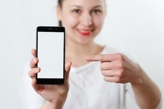 Young woman holding a smartphone with a white screen in front of her, pointing at it with her finger