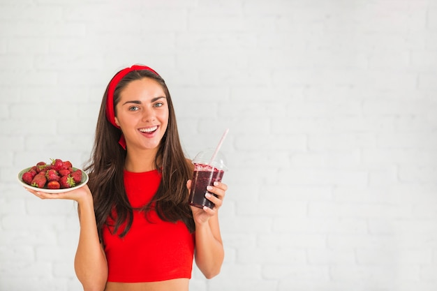 Young woman holding smoothies and plate of strawberry