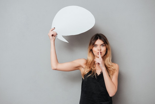 Young woman holding speech bubble and showing silence gesture