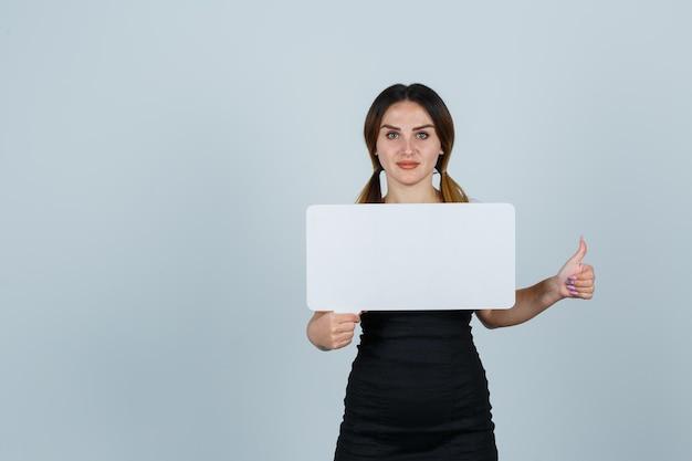 Giovane donna che tiene il fumetto mentre mostra i pollici in su