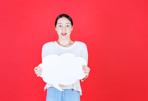 Молодая женщина, держащая речи пузырь с формой облака