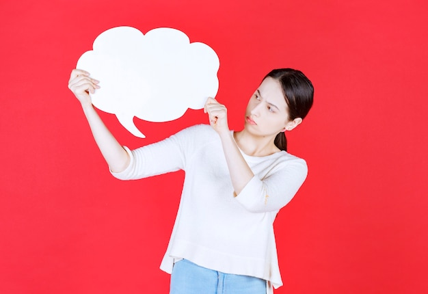 Young woman holding speech bubble with a cloud shape