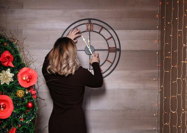時計の近くに立っている若い女性は、ほぼ12を示しています。壁に時間を設定します。
