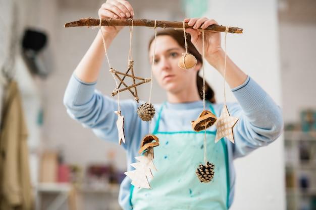 Молодая женщина, держащая палку с рождественскими украшениями из картона ручной работы и шишками, висящими на нитках