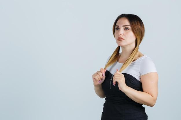 Giovane donna che tiene ciocche di capelli mentre pensa a qualcosa