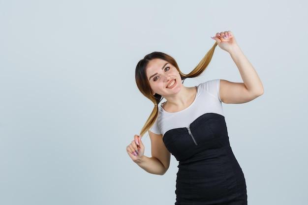 Молодая женщина держит пряди волос и выглядит веселой