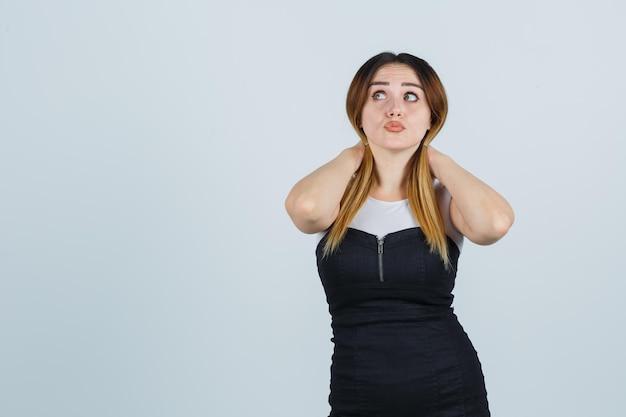 Молодая женщина, держащая пряди волос и задумчивая