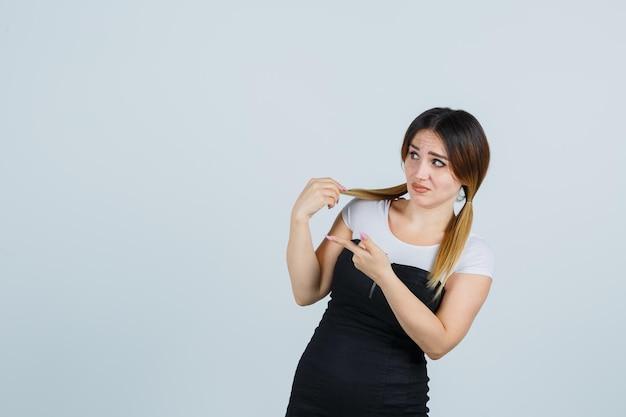 Молодая женщина, держащая пряди волос и указывающая на левую сторону