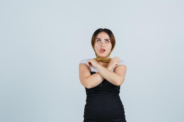 Молодая женщина, держащая пряди волос и высунувшая язык