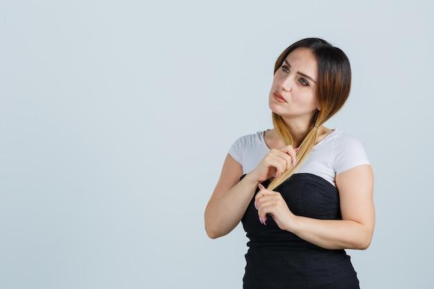 Молодая женщина держит пряди волос, думая о чем-то
