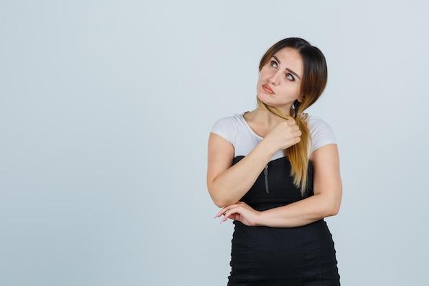 Молодая женщина, держащая пряди волос